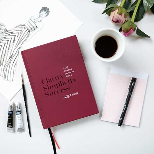 Display with pink roses, pink notepad, fashion illustration showing the burgundy front cover of Clarity Simplicity Success A Self Coaching Journal for Women by Jacqui Alder