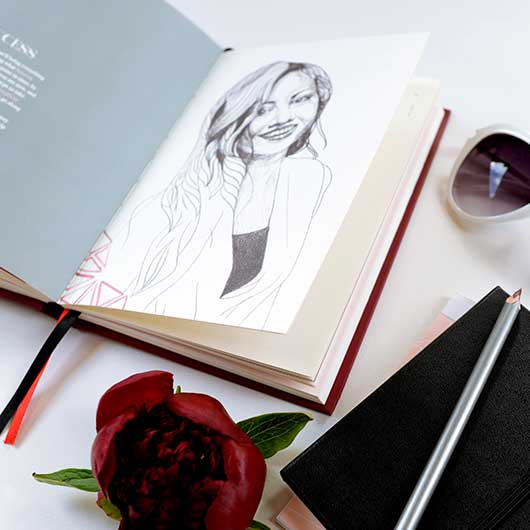 Flatlay photo of success journal showing gashion drawing of a smiling woman and words under the title SUCCESS. Next to