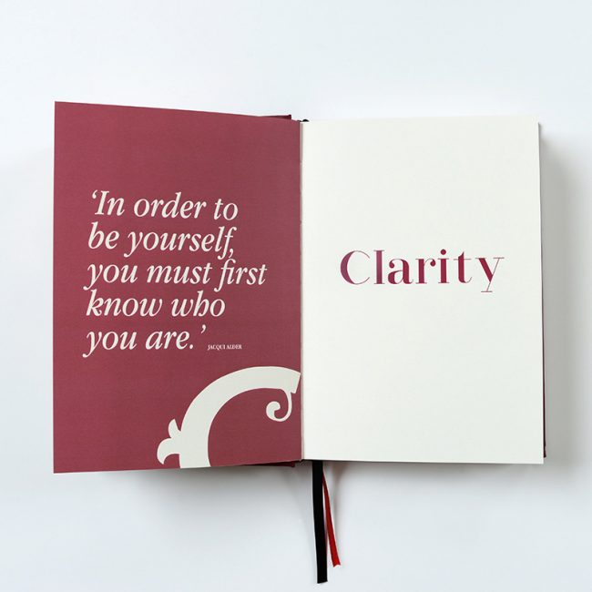 Burgundy page with quote 'In order to be yourself you must first know who you are.' with the word Clarity printed in burgundy on the opposite page showing a look inside Clarity Simplicity Success Journal for Women.