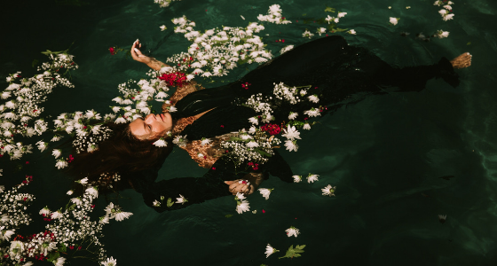 Dark green pool of water with woman wearing a black dress flaoting on on her back amongst floating white ad red flowers