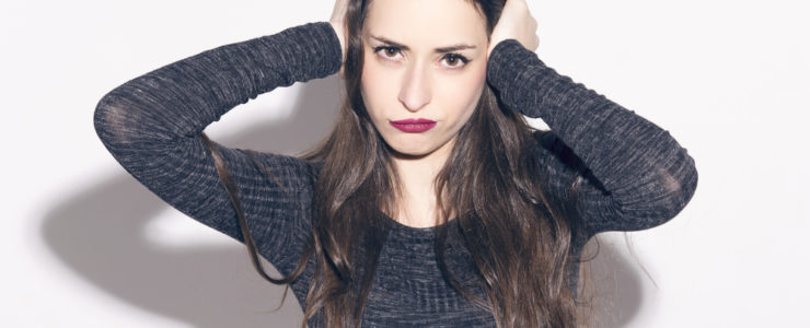 Young caucasian woman wearing long sleeved grey top with an sassy expression on her face and her hands over her ears