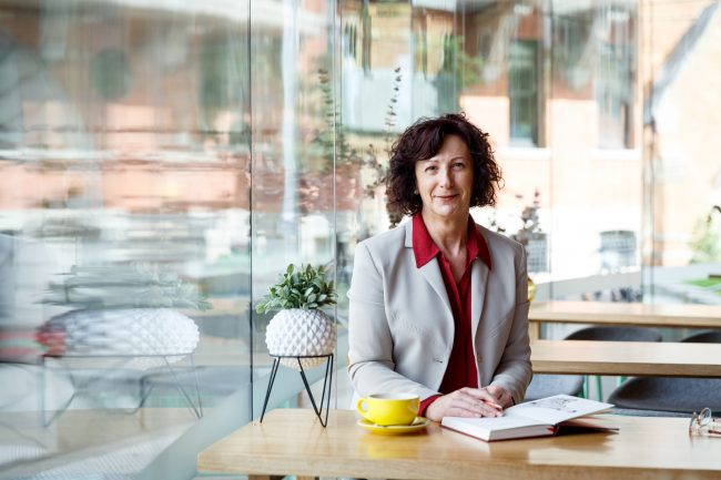 A smiling Jacqui Alder seated in a cafe