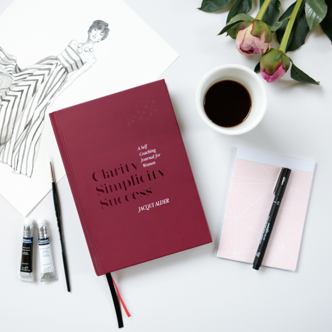 Burgundy coloured front cover of Clarity Simplicity Success A Self Coaching Journal for Women by Jacqui Alder on a desk with a beautiful fashion sketch and pink roses