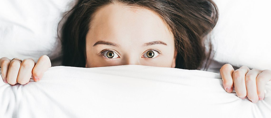 Young caucasian women with brown hair and hazel eyes lying in bed amongst white sheets hold the covers over her face until just under her eyes. She is wearing a 'I don't want to get out of bed' expression